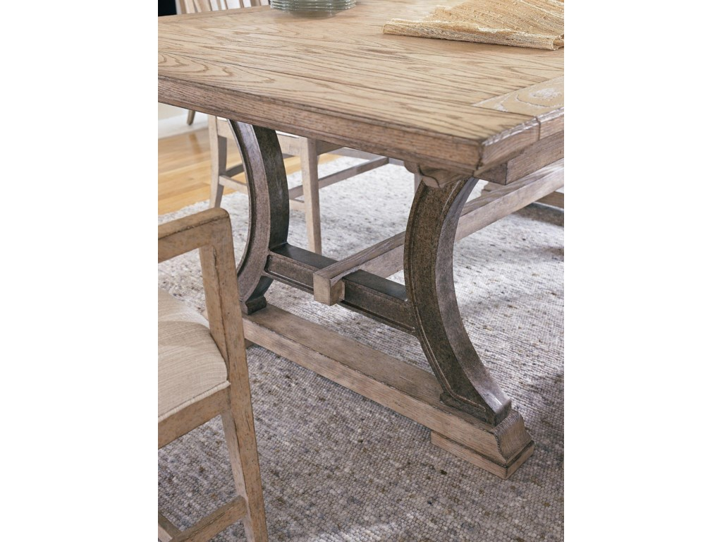 An antiqued pewter trestle base combined with a Weathered Pier finish lend an industrial feel to the Shelter Bay Table.